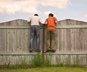 two people peering over fence